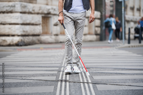 Midsection of young blind man with white cane walking across the street in city Fototapet