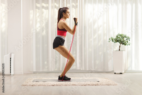 Stampa su Tela Young woman exercising with resistance band at home