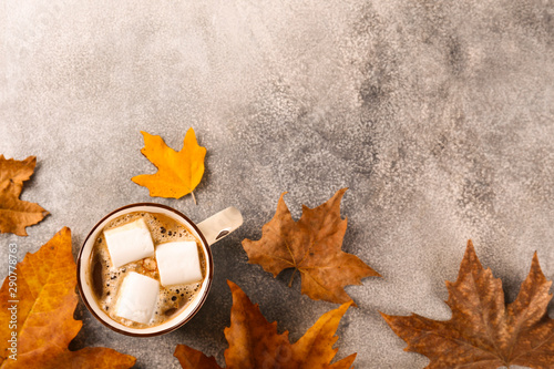 Wallpaper Mural Top view composition with vintage styled cup of coffee with marshmallows and autumn themed decoration, fallen leaves on textured background