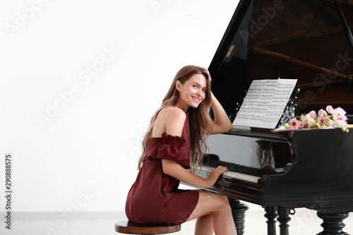 Wallpaper Mural Beautiful young woman at grand piano
