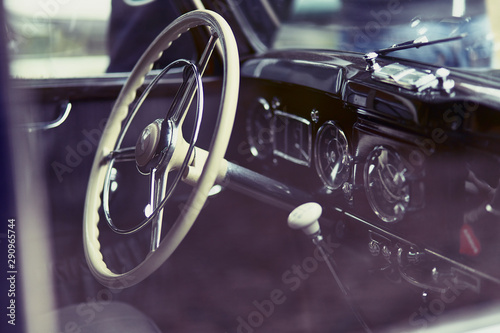 Fototapeta Close-up of the cockpit of a classic car showing steering wheel and gear
