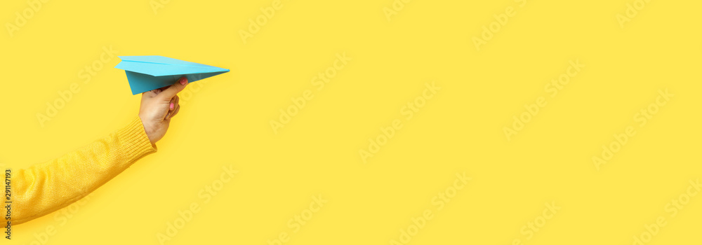 hand holding paper plane over yellow background, panoramic mock up image