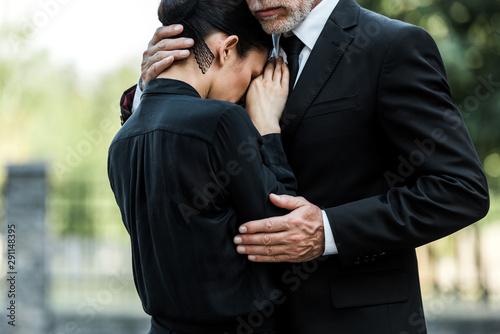 Fototapeta cropped view of sad elderly man embracing woman on funeral