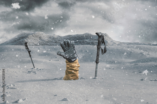 Leinwand Poster Hiker stretching out his snow covered hand next to trekking poles to signal help because of snow avalanche