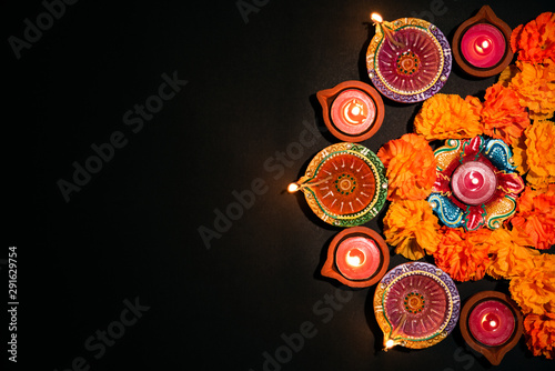 Happy Diwali - Clay Diya lamps lit during Dipavali, Hindu festival of lights celebration. Colorful traditional oil lamp diya on white background