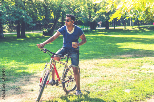 Fototapeta Young Indian man on bicycle with smartphone