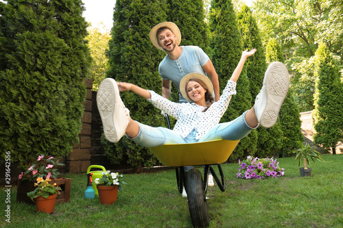 Happy couple having fun while working together in garden Fototapete