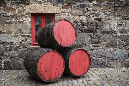 Leinwand Poster Whisky barrels in front of a historic wall.