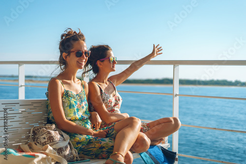 Canvas Print Two young women girl friends or sisters sitting on the bench on the deck of the