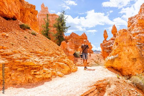 Man tourist person walking by orange color formations at Queens Garden Navajo Lo Fotobehang