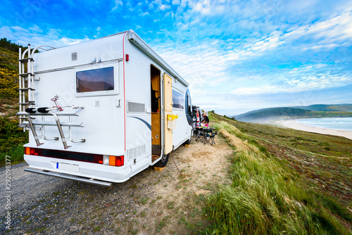 Motorhome RV and campervan are parked on a beach. Fototapeta