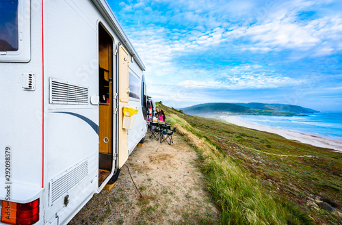 Fotografie, Tablou Motorhome RV and campervan are parked on a beach.