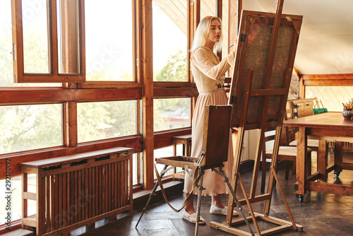 Fotografia, Obraz Beautiful talented young woman artist paints a picture with brush and oil on an