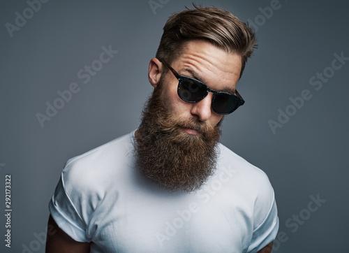 Obraz na plátně Stylish young hipster with a long beard wearing sunglasses