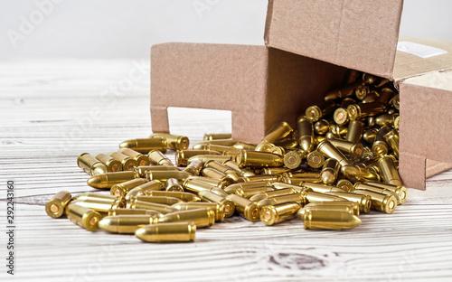 Fotografia Yellow brass gun ammo spilled from paper carton box on white boar desk - close u
