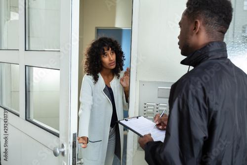 Woman Opening Door To Bailiff Fototapeta