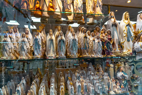 Fototapeta statues or figurines in a shop, the commercial side of Lourdes.