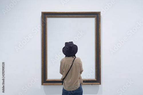 Fototapeta interior view of a lonely girl or tourist looking at blank canvas at a museum or gallery