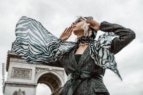 Fototapeta Outdoor autumn fashion portrait of elegant, luxury lady wearing trendy black boucle blazer, wide leather belt, animal, zebra print silk scarf, posing near Triumphal Arch in Paris