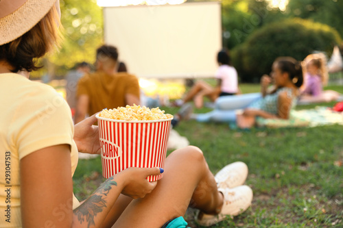 Fototapeta Young woman with popcorn watching movie in open air cinema, closeup