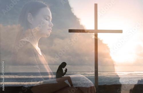 Fototapeta Religious woman praying to god next to a cross, peaceful nature.