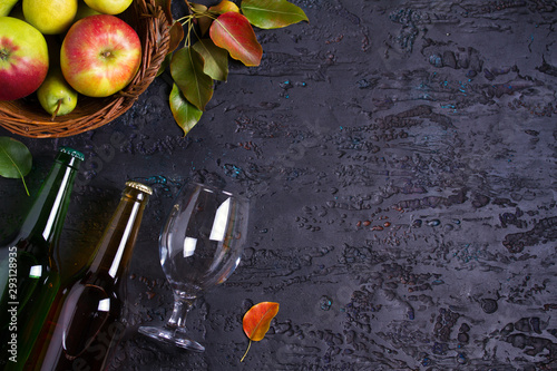 Fotografia Bottles and glass of apple and pear cider with fruits on black background