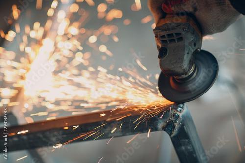 Obraz na plátne Craftsman sawing metal with disk grinder saw in workshop