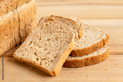 Fotografia Three slices of whole wheat toast bread isolated on light wood next to a loaf of bread