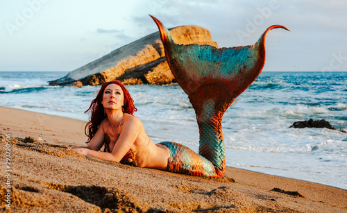 Canvas Print Caucasian redhead woman with mermaid tail reclines on the beach in the waves