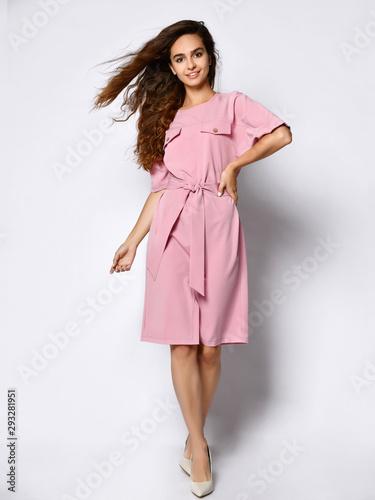Obraz na płótnie Full length portrait of happy beautiful woman in pink dress posing in studio iso