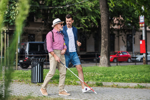 Tablou Canvas Young man and blind senior with white cane walking on pavement in city