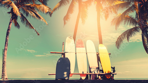 Canvas Print Surfboard and palm tree on beach background.