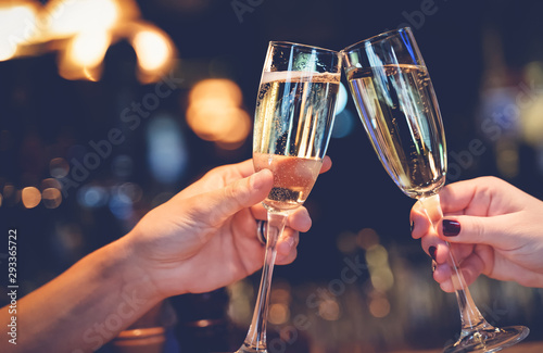 Obraz na plátně Two glasses with sparkling champagne wine in hands, concept for holiday, wedding