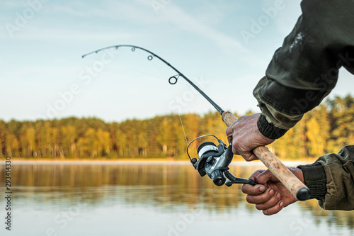 Fotografía Hands of a man in a Urp plan hold a fishing rod, a fisherman catches fish at dawn