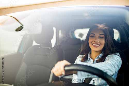 Fotografering Beautiful young happy smiling woman driving her new car at sunset