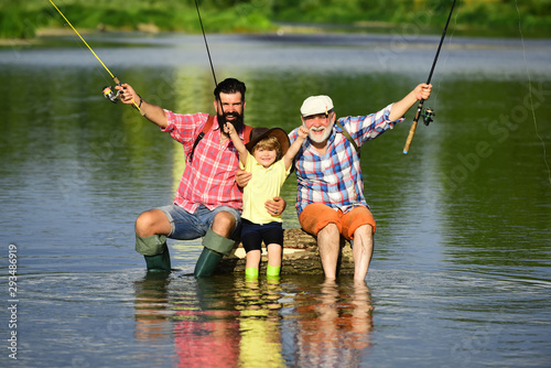 Canvas-taulu Happy grandfather and grandson are fishing on the river