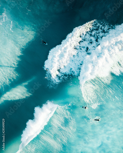 Fotografia Surfers enjoying massive waves at sunrise in the ocean