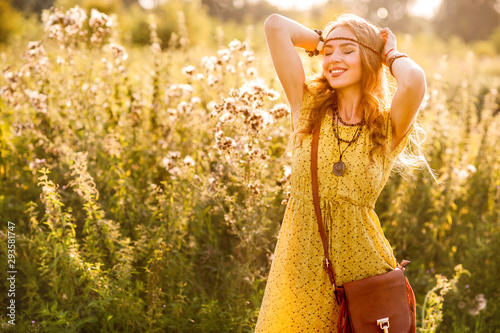 Photo Smiling bohemian girl in yellow dress with guitar on the field at sunset warm li