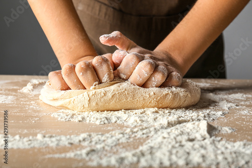 Fotografiet Woman kneading flour in kitchen, closeup