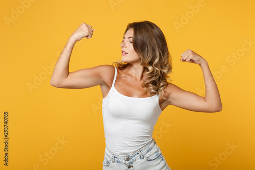 Canvas Strong young woman girl in light casual clothes posing isolated on yellow orange wall background studio portrait