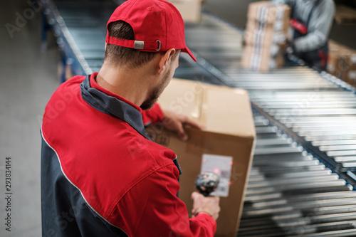 Obraz na płótnie Warehouse worker working on a conveyor line