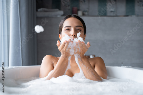 Leinwand Poster Relaxed young woman taking a bath with foam