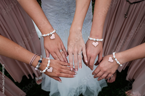 Photographie Four woman's hand with heart bracelet