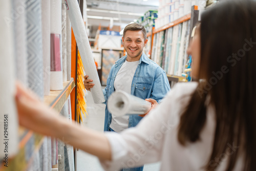 Young couple buying wallcovering in hardware store