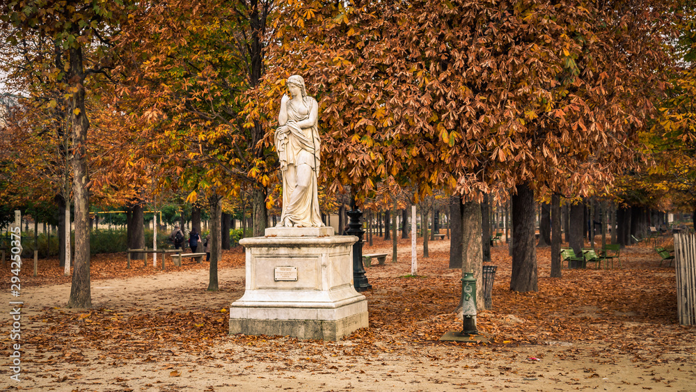 Alley of the Jardin des Tuileries covered with orange autumn leaves, statue in the Tuileries garden in Paris France on a beautiful Fall day <span>plik: #294250375 | autor: JeanLuc Ichard</span>