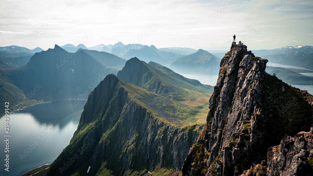 Żądny przygód mężczyzna stoi na szczycie góry i cieszy się pięknym widokiem podczas tętniącego życiem zachodu słońca. Podjęte na szczycie Senja, Norwegia <span>plik: #294399142 | autor: Pavel Kašák</span>