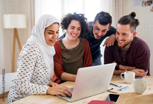Tableau sur Toile A multi-ethnic group of young friends with laptop indoors, house sharing concept