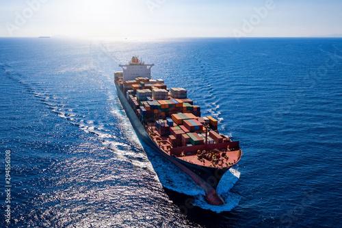 Photo Luftaufnahme ein beladenen Containerschiffes bei voller Fahrt über blauem Meer