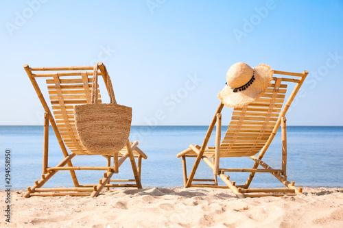 Wooden deck chairs on sandy beach near sea Fototapet