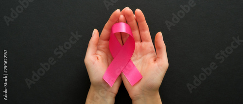 Canvas Print Breast cancer awareness symbol pink ribbon in woman hands on black background